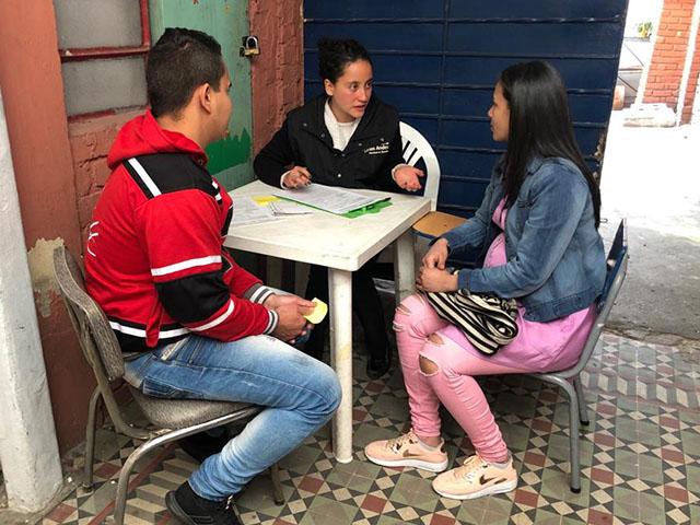 Atención a población migrante venezolana. Una estudiante atendiendo a una pareja conformada por un hombre y una mujer embarazada.