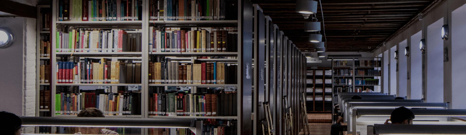 Biblioteca Satélite de Derecho Eduardo Álvarez-Correa. Interior de la biblioteca, estantes con libros, algunos estudiantes en la biblioteca.